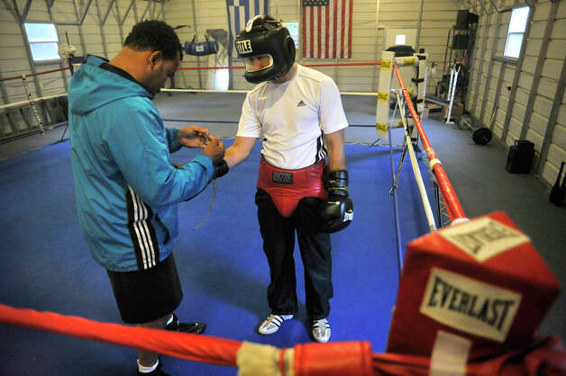 Trainer Fernely Feliz, left, laces up Delvin Rodriguez's boxing gloves before sparring at their training camp in North Hudson, N.Y., on Tuesday, May 8, 2012. The Dominican-born and Danbury-raised Delvin Rodriguez will fight Austin Trout on June 2 for the World Boxing Association junior middleweight world championship. Photo: Jason Rearick / The News-Times