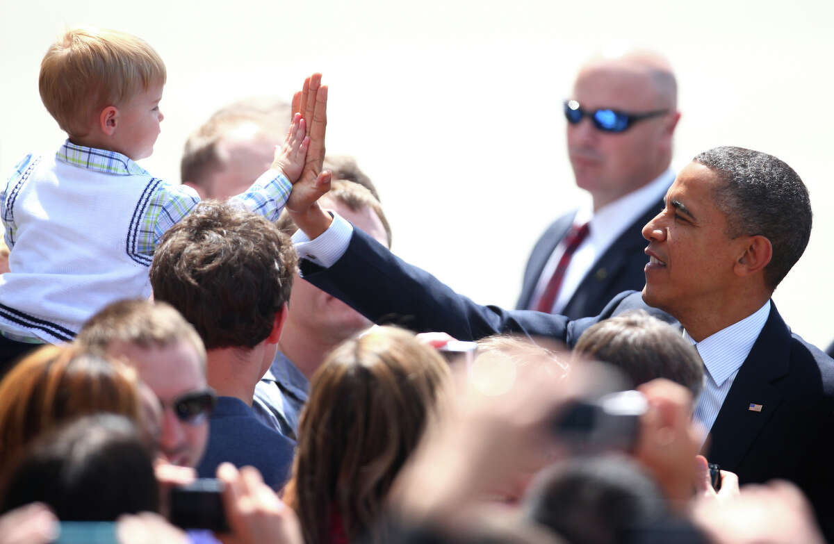 U.S. President Barack Obama high-fives a young supporter as Air Force One lands at Boeing Field during a visit to Seattle on Thursday . The president was scheduled to attend two fund raisers during the visit.