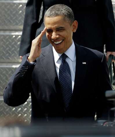 President Barack Obama salutes as he arrives in Seattle on Thursday. Obama was in town for fund-raising events. Photo: AP