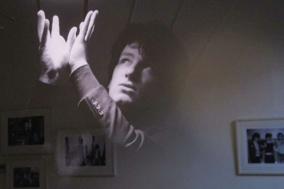 With other photos reflected behind, a February 1979 photo of an 18-year-old Bono posing under a fluorescent light is one of the more striking images from the ''U2 1978-1981'' exhibition opening in Dublin, Ireland, on Thursday, May 10, 2012.  The Little Museum of Dublin is displaying a collection of pictures by photographer Patrick Blocklebank, documenting the gritty beginnings of U2 in the smoky pubs and clubs of Dublin before the Irish band became the international supergroup of today.  (AP Photo/Shawn Pogatchnik) Photo: Shawn Pogatchnik / AP