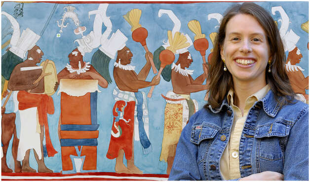 Heather Hurst, assistant professor of anthropology at Skidmore College, with reproductions she created of Maya murals from one of her archaeological expeditions. (Skidmore College photo)