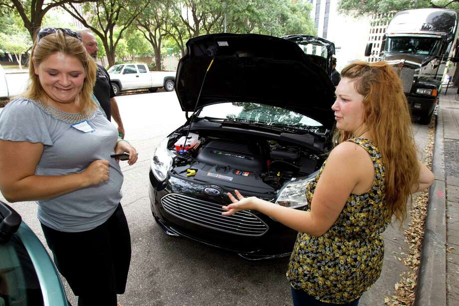 Kristi Reddell, left, and Taylor Nixon talked about  new 2012 Ford Focus Electric near City Hall Thursday, May 10, 2012, in Houston. The battery-powered cars were on display and test drives were offered at Hermann Square Park. The zero-emission, all-electric Ford Focus Electric is expected to arrive in local Ford showrooms in several weeks to several months, Ford spokesman Nik Ciccone said. Photo: Brett Coomer, Houston Chronicle / © 2012 Houston Chronicle