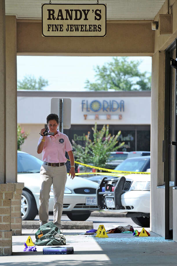 A Beaumont Police crime scene investigator video records evidence from a robbery-turned-shootout at Randy's Fine Jewelers on Wednesday. During the attempted robbery, store owner Randy Flatau shot the thief four times in the upper body. Flatau was also shot in the leg once. Both men are said to be in stable condition.  Photo taken Wednesday, May 9, 2012 Guiseppe Barranco/The Enterprise Photo: Guiseppe Barranco, STAFF PHOTOGRAPHER / The Beaumont Enterprise