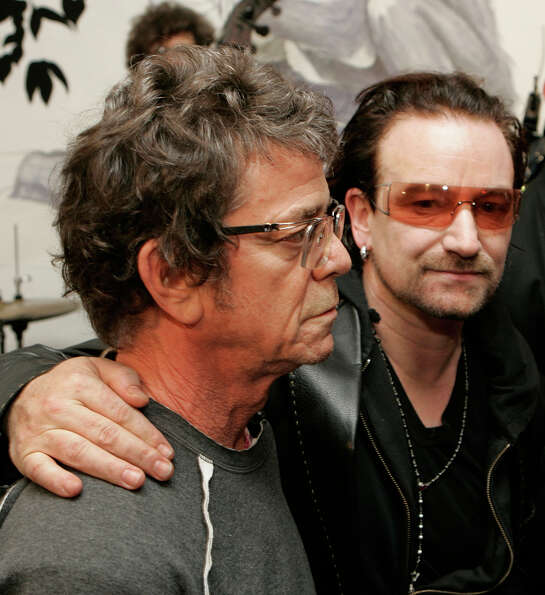 U2 lead singer Bono, right, embraces musician Lou Reed at a party presenting fall fashions from the