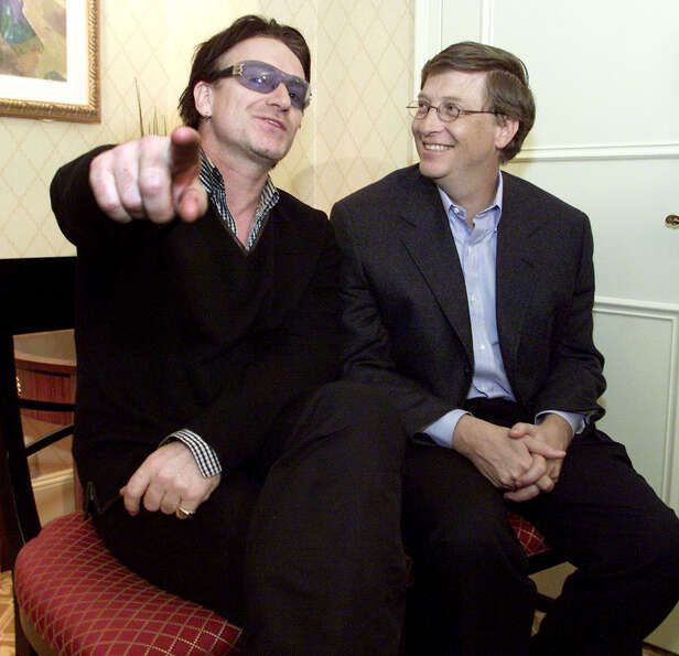 Bono, left, lead singer of the band U2, and Microsoft Corp. Chairman Bill Gates sit together before