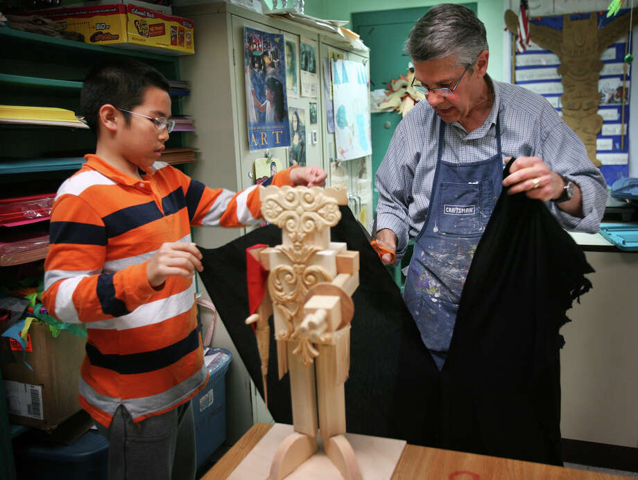 "Fifth grader Graham Chen, 10, gets assistance making a cape for his ""fighter robot"" sculpture from his art teacher Frank Vespi at Orchard Hills Elementary School in Milford on Thursday, May 10, 2012. Vespi, the Milford Art Department chaiman, is retiring. Photo: Brian A. Pounds / Connecticut Post"
