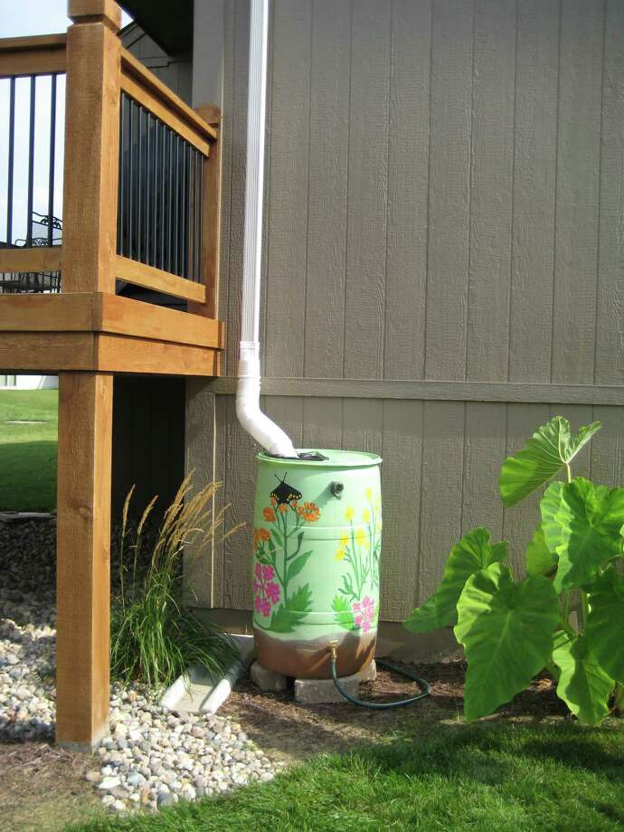 "In this Sept. 13, 2009 image released by Alice Snider, a decorated rain barrel, ""Butterfly Garden,""  is connected to a downspout in a backyard, where it will capture rainwater for watering garden beds. Rain barrel usage is on the rise around the country, according to gardening and conservation experts.  (AP Photo/Alice Snider) Photo: Alice Snider"