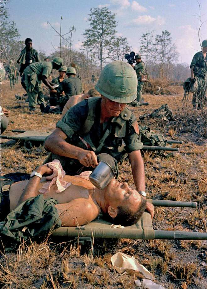 In this April 2, 1967 file photo shot by Associated Press photographer Horst Faas, a wounded U.S. soldier is given water on a battlefield in Vietnam. Faas, a prize-winning combat photographer who carved out new standards for covering war with a camera and became one of the world's legendary photojournalists in nearly half a century with The Associated Press, has died Thursday May 10, 2012. He was 79. (AP Photo/Horst Faas) Photo: Horst Faas, Associated Press / AP