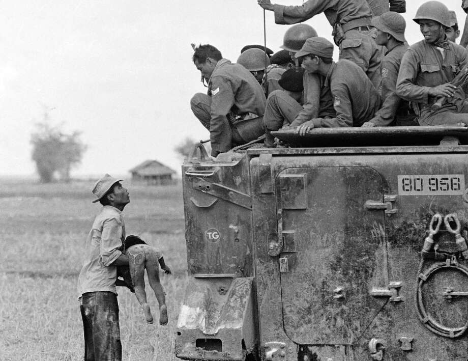 In this March 19, 1964 file photo, one of several shots by Associated Press photographer Horst Faas which earned him the first of two Pulitzer Prizes, a father holds the body of his child as South Vietnamese Army Rangers look down from their armored vehicle. The child was killed as government forces pursued guerrillas into a village near the Cambodian border. Faas, a prize-winning combat photographer who carved out new standards for covering war with a camera and became one of the world's legendary photojournalists in nearly half a century with The Associated Press, died Thursday May 10, 2012. He was 79. (AP Photo/Horst Faas) Photo: HORST FAAS, Associated Press / AP
