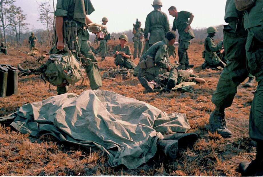 In this April 2, 1967 file photo shot by Associated Press photographer Horst Faas, a dead U.S. soldier lays on the battlefield with a sheet over him in Vietnam. Faas, a prize-winning combat photographer who carved out new standards for covering war with a camera and became one of the world's legendary photojournalists in nearly half a century with The Associated Press, Thursday May 10, 2012. He was 79. (AP Photo/Horst Faas) Photo: Horst Faas, Associated Press / AP