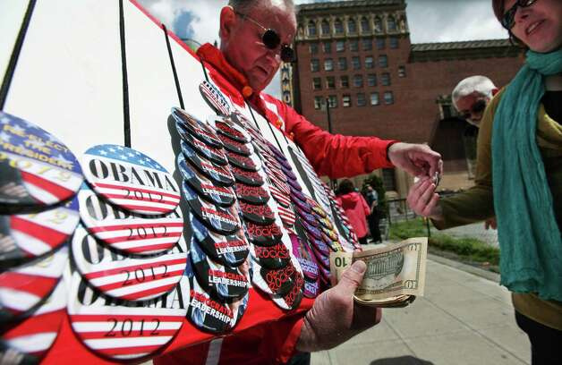 Marty Miller sells campaign buttons supporting President Barack Obama outside a fund-raising event for the president, Thursday in Seattle. Miller sold similar badges in support of then-candidate Newt Gingrich at another recent Seattle-area event. Photo: AP