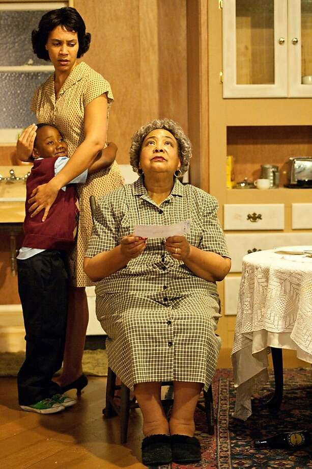 """Family matriarch Lena Younger (Eleanor Jacobs, seated) gets a big insurance settlement as daughter-in-law Ruth (Leontyne Mbele-Mbong)and little Travis (Zion Richardson) look on in African-American Shakespeare Company's production of """"A Raisin in the Sun"""" Photo: Lance Huntley"""