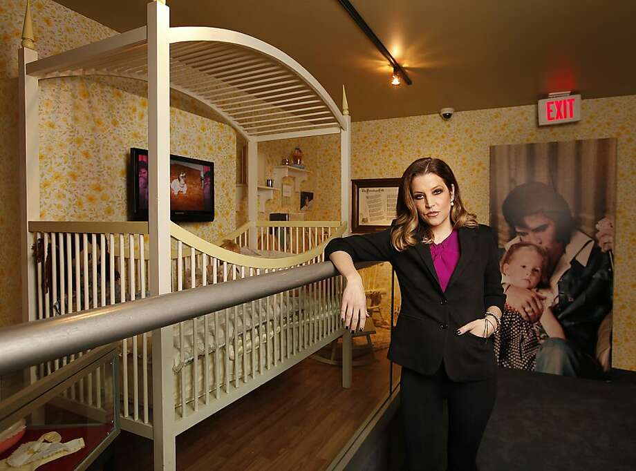 "In this Tuesday, Jan. 31, 2012 photo, Lisa Marie Presley stands next to her childhood crib displayed with other mementos in the new exhibit ""Elvis Through His Daughter's Eyes"" which opens Wednesday, Feb. 1, 2012 at Graceland in Memphis, Tenn. She was born on Feb. 1, 1968. (AP Photo/Lance Murphey) Photo: Lance Murphey, Associated Press"