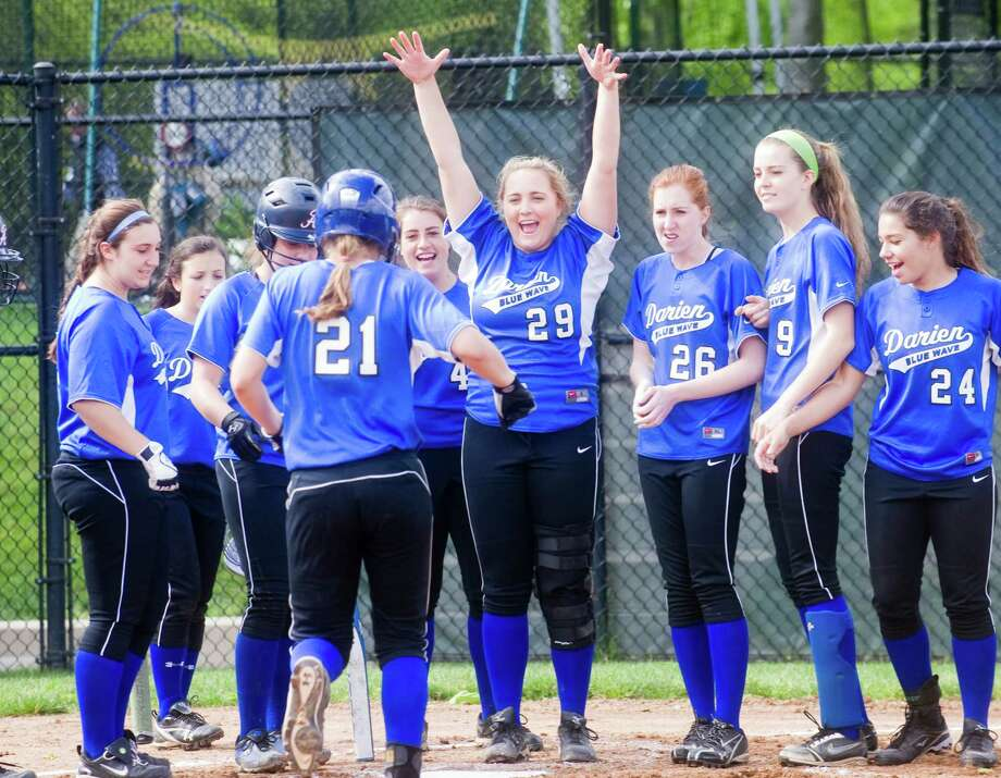 Darien's Erika Osherow  is greeted by teammates led by Brittany Osborn, center, as she brings in a homer as Darien High School hosts Stamford High in a softball game in Darien, Conn., May 10, 2012. Photo: Keelin Daly / Stamford Advocate