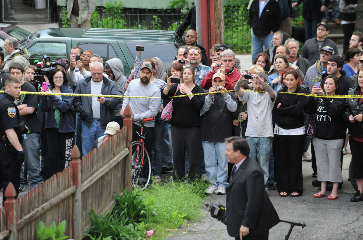 A crowd of onlookers try to get a glimps of a bear in a tree near North College St. in the Stockade Thursday, May 10, 2012 in Schenectady, N.Y. (Lori Van Buren / Times Union)