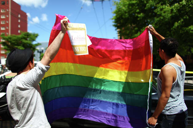 Gay rights supporters hold a flag as U.S. President Barack Obama arrives for a fund raiser at the Paramount Theater in Seattle on Thursday, May 10, 2012 . A day earlier the president came out in support of gay marriage rights. The president attended two fund raisers during the Seattle visit. Photo: JOSHUA TRUJILLO / SEATTLEPI.COM