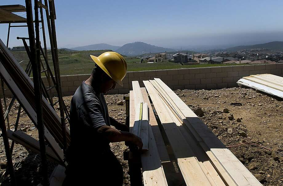 A laborer measures wood while working on a home in the San Elijo Hills of San Diego, where new homes are in demand but finished lots are rare. Photo: Sam Hodgson, Bloomberg