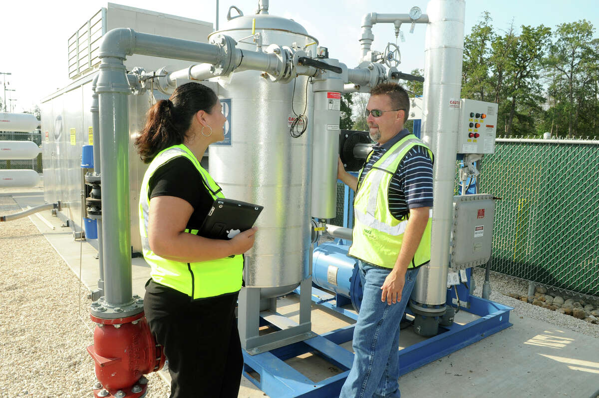 Waste Management community relations staff member Debbie Figueras-Cano gets a tour of the new Conroe compressed natural gas station from Waste Management's Scott Graefing.