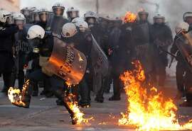 In this Sunday, Feb. 12, 2012, file photo, riot police officers try to extinguish flames from a petrol bomb thrown by protestors outside the Greek parliament, in Athens.  Austerity has been the main prescription across Europe for dealing with the continent's nearly 3-year-old debt crisis, brought on by too much government spending. Greece, one of three eurozone nations to need an international bailout, has cut spending on just about everything it can public sector salaries, pensions, education, health care and defense. (AP Photo/Thanassis Stavrakis)