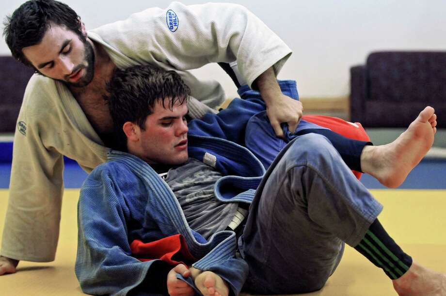 Burnt Hills graduate Nick Delpopolo, bottom, hopes to make the U.S. Olympic team in judo, and has to win a bout on Saturday to qualify. He and Tony Sangimino, top, do newaza, or mat work, at the Jason Morris Judo Center on Monday night May 7, 2012 in Glenville, NY.(Philip Kamrass / Times Union ) Photo: Philip Kamrass / 00017543A