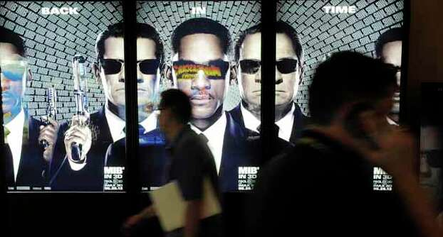 """Convention attendees blur past an advertisement for the upcoming film """"Men in Black III"""" on the opening day of CinemaCon 2012, the official convention of the National Association of Theater Owners, Monday, April 23, 2012. Photo: Chris Pizzello, . / AP"""