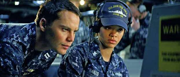 """In this film publicity image released by Universal Pictures, Taylor Kitsch, left, and Rihanna are shown in a scene from """"Battleship."""" �Battleship,� a Universal Pictures movie based on the Hasbro Inc. board game, has survived an armada of tomato-throwing critics and chugged to $170 million in ticket sales overseas. The haul goes part way to justifying the reported $209-million price tag, but after subtracting splits with theater owners, it is estimated to need about half a billion at box offices to turn a profit. With a fleet of other hotly expected blockbusters surrounding its U.S. release on May 18, the tides need to be solidly in its favor to stay above water. Photo: Photo Credit: ILM/Universal Pict, . / Copyright: © 2012 Universal Studios. ALL RIGHTS RESERVED."""