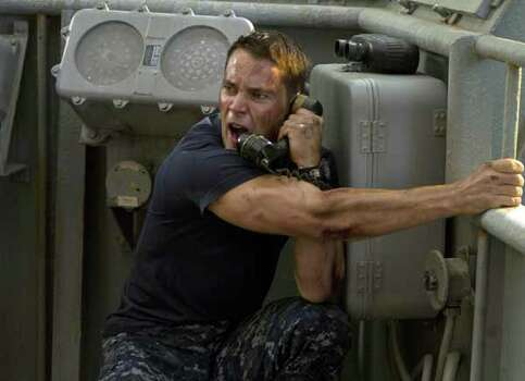 """In this film image released by Universal Pictures, Taylor Kitsch is shown in a scene from """"Battleship."""" The Hasbro Inc. game using plastic pegs and ships was once a way for kids to while away lazy summer afternoons. But as it debuts in Europe on April 11, �Battleship� the movie has become a potential franchise sporting Michael Bay-inspired special effects, aliens invading Earth, a bikini-model actress, superstar Rihanna and, of course, lots of guns. Photo:  Frank Masi, . / Copyright: © 2012 Universal Studios. ALL RIGHTS RESERVED. Copyright: © 2012 Universal Studios. ALL RIGHTS RESERVED."""