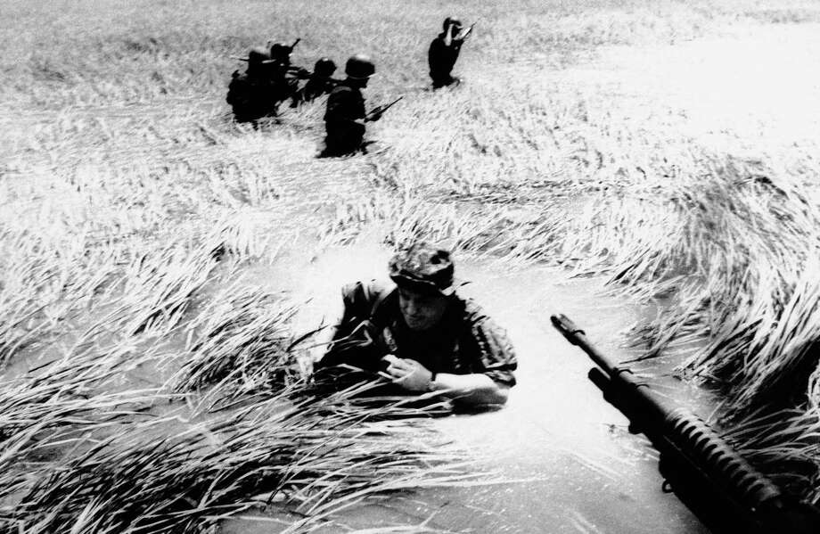 In this May 11, 1965 file photo, Associated Press photographer Horst Faas tries to get back on a U.S. helicopter after a day out with Vietnamese rangers in a flooded plain of reeds. Photo: Associated Press / AP
