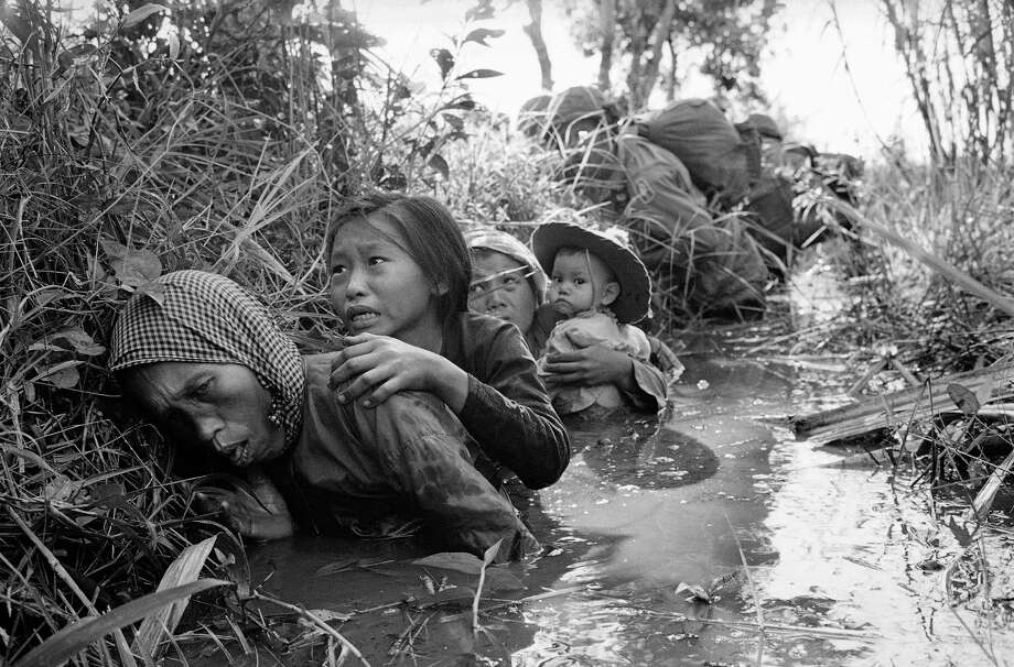In this Jan. 1, 1966 file photo taken by Associated Press photographer Horst Faas, women and children crouch in a muddy canal as they take cover from intense Viet Cong fire at Bao Trai, about 20 miles west of Saigon, Vietnam. Photo: HORST FAAS, Associated Press / 1966 AP