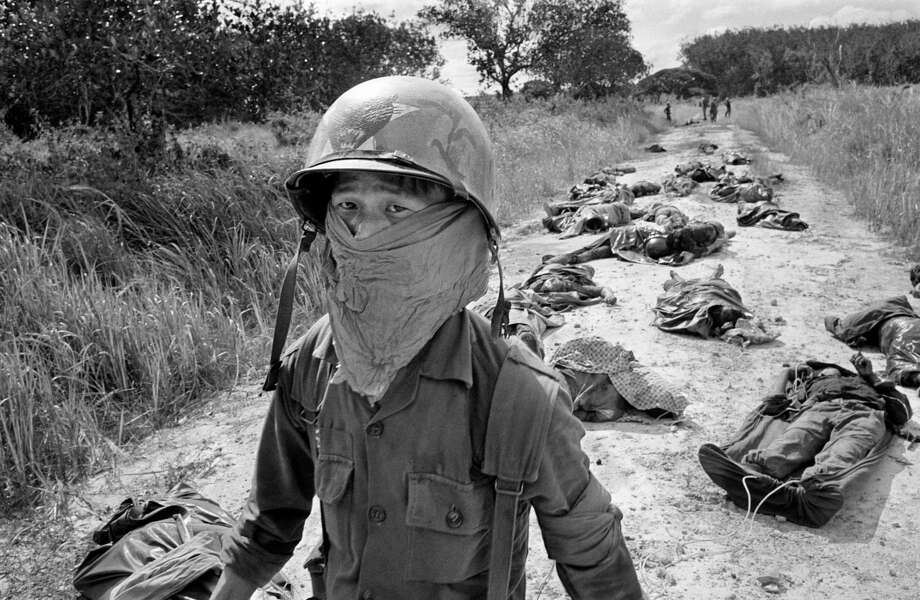 In this Nov. 27, 1965 file photo taken by Associated Press photographer Horst Faas, a Vietnamese litter bearer wears a face mask to keep out the smell as he passes the bodies of U.S. and Vietnamese soildiers killed in fighting against the Viet Cong at the Michelin rubber plantation, about 45 miles northeast of Saigon. Photo: Horst Faas, Associated Press / AP1965