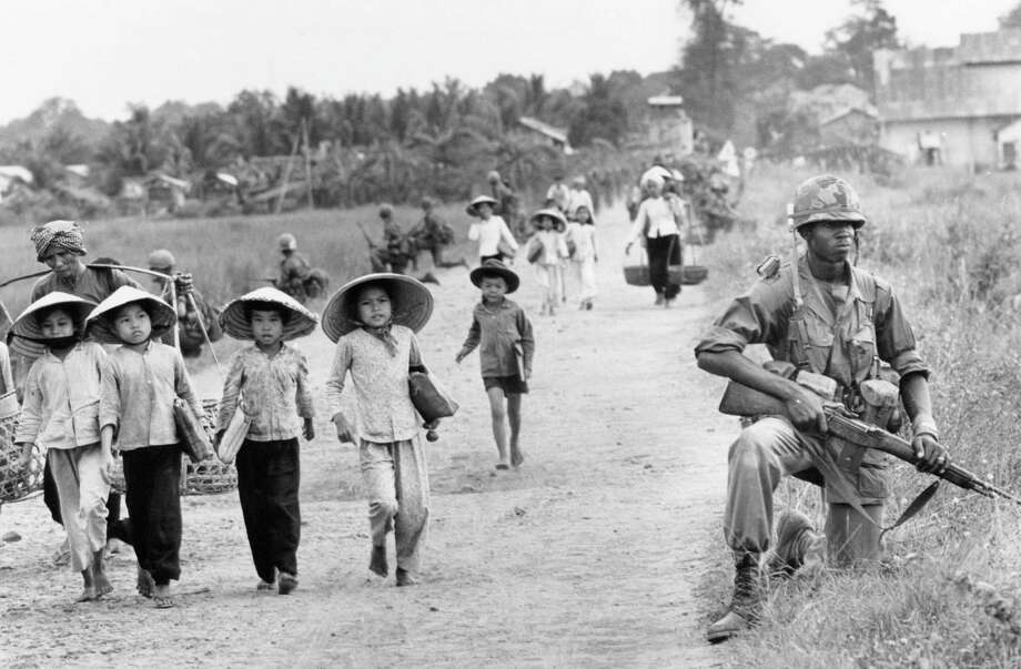 In this December 1965 file photo shot by Associated Press photographer Horst Faas, a U.S. 1st Division soldier guards Route 7 as Vietnamese women and school children return home to the village of Xuan Dien from Ben Cat, Vietnam. Photo: Horst Faas, Associated Press / AP1965