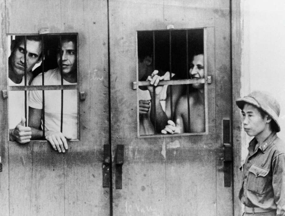 In this March 1973 file photo taken by Associated Press photographer Horst Faas, American prisoners of war look through barred wooden doors at the last detention camp at Ly Nam De Street in Hanoi, North Vietnam. Photo: Horst Faas, Associated Press / AP