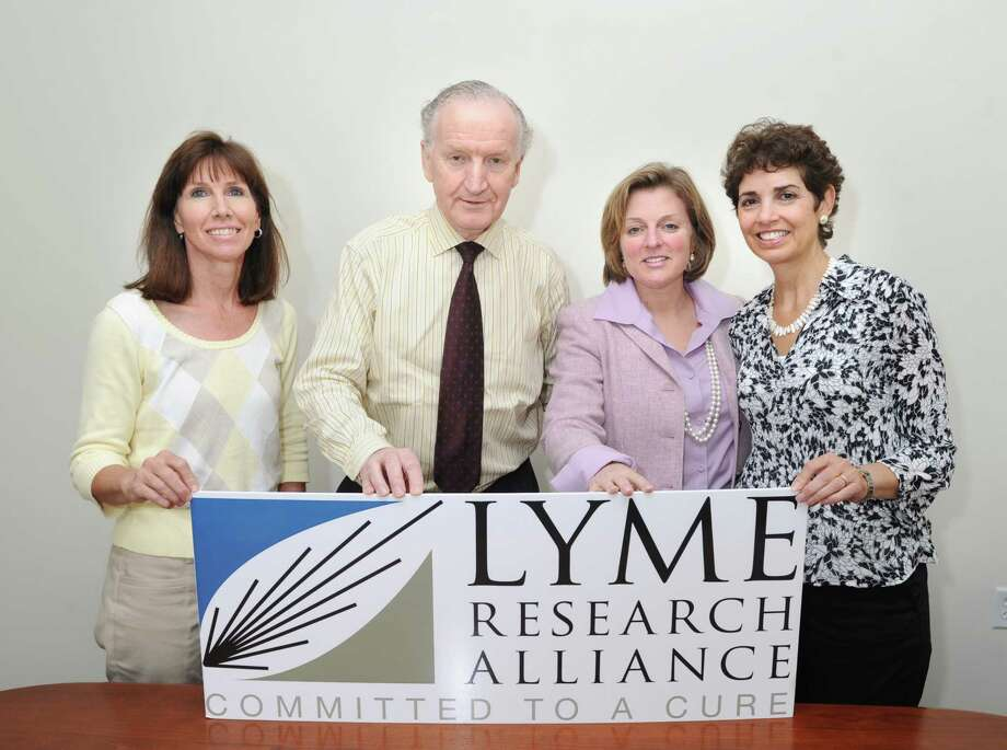 Members of Lyme Research Alliance from left, Fran Herzog, Executive Director Peter Wild, Debbie Siciliano and Diane Blanchard with their newly fabricated sign in their Stamford office, Wednesday afternoon, May 9, 2012. The organization was previously named Time for Lyme, but has changed its name to more accurately reflect its mission to fund and promote research and education about Lyme and other tick-borne diseases. Photo: Bob Luckey / Greenwich Time