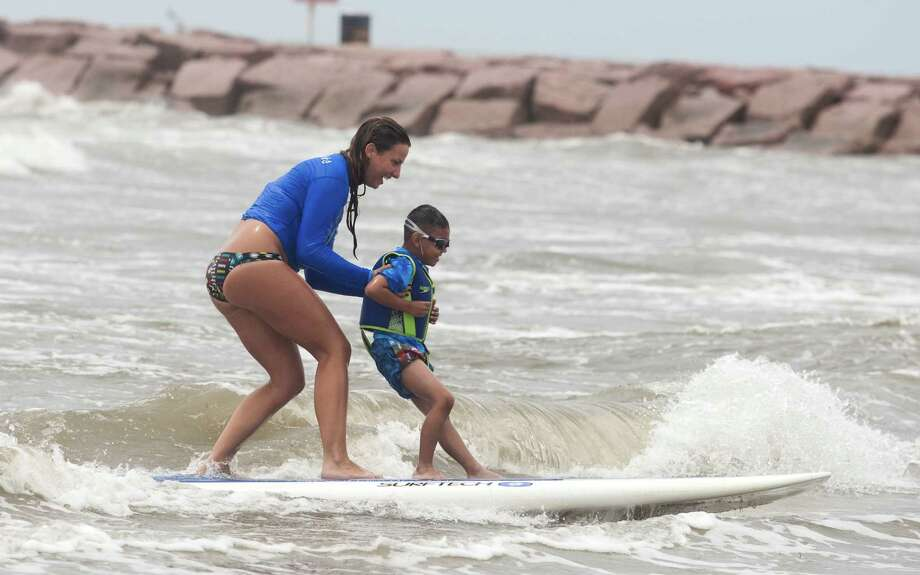 Volunteer Andi Fogel helps Apollo Contreras, 5, catch a wave during the Waves of Impact free surf camp for children with autism at Seawall Blvd. on Thursday, May 10, 2012 in Galveston, Texas.  Several dozen children with autism and their families participated in the event that was designed to be a therapeutic surfing experience. This was Apollo's first time to surf, but he had been watching it on youtube and was ready for the challenge. Photo: J. Patric Schneider, For The Chronicle / Houston Chronicle