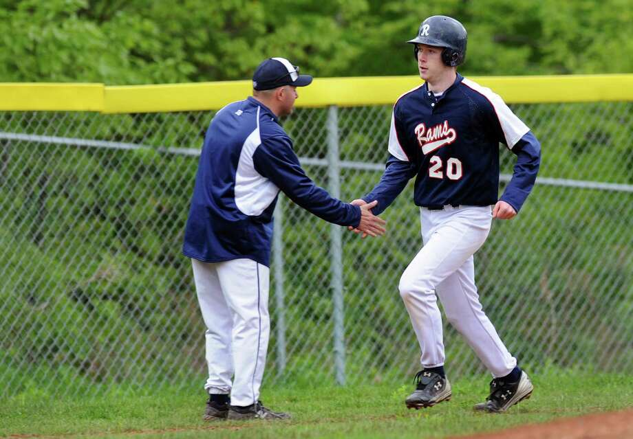 Rensselaer's assistant coach Dave Martyn, left, congratulates Isaac Goca (20) as he runs the bases after hitting a home run during their baseball game against Germantown on Thursday, May 10, 2012, at Rensselaer High in Rensselaer, N.Y. (Cindy Schultz / Times Union) Photo: Cindy Schultz / 00017590A