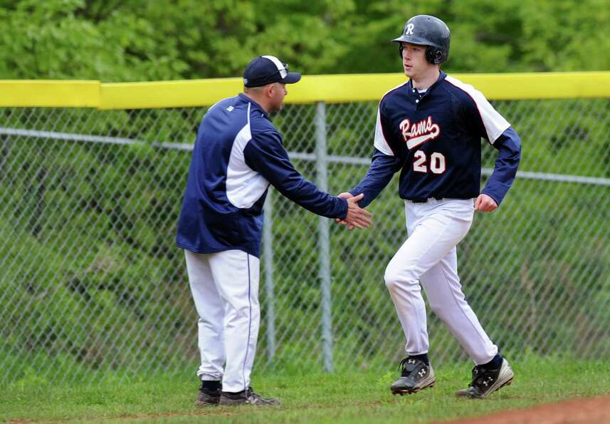 Rensselaer's assistant coach Dave Martyn, left, congratulates Isaac Goca (20) as he runs the bases a