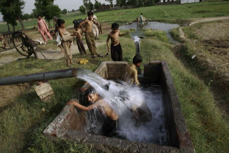 Pakistani boys swim in a water reservoir to cool off as the temperature rises, on the outskirts of Gujranwala, in Punjab province, Pakistan, Thursday, May 10, 2012. (AP Photo/Muhammed Muheisen) Photo: Muhammed Muheisen, Associated Press