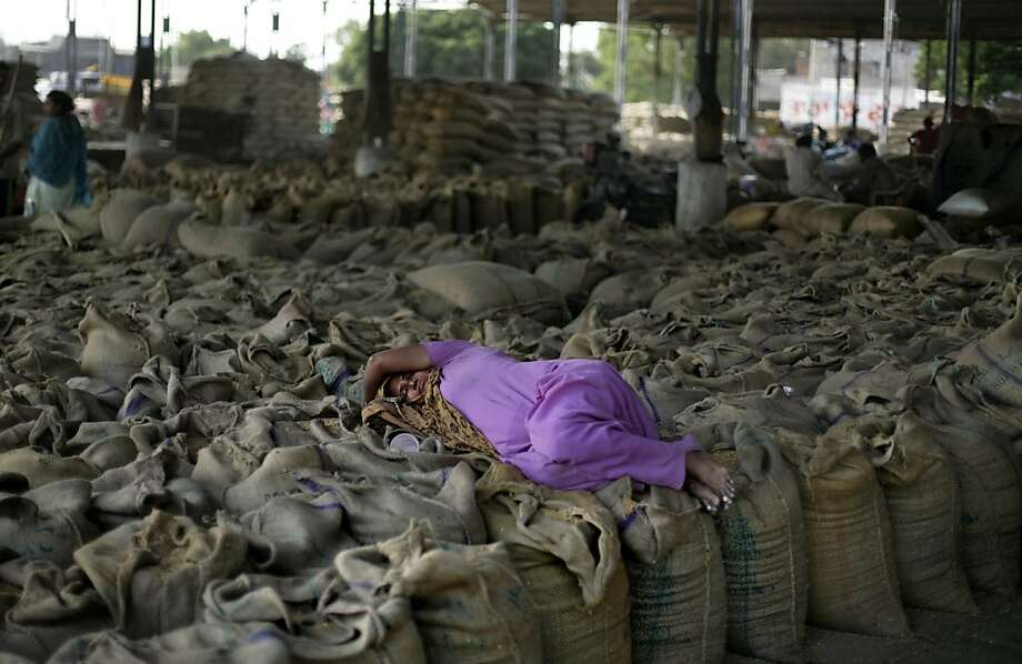 In this photo taken Thursday, May 3, 2012, an Indian laborer sleeps on jute bags containing wheat grain at a grain market in Amritsar, India. Four bumper harvests over the past five years have swelled food grain production across the country. The government has been reluctant to allow grain exports for fear of political protests at a time when it has been dogged by double digit food inflation for months. Nearly half of India's children under age five are malnourished. (AP Photo/Altaf Qadri) Photo: Altaf Qadri, Associated Press