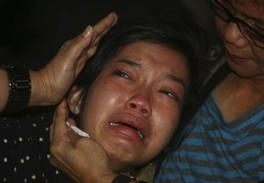 A relative weeps as she waits for the latest news on the Russian passenger jet that crashed into a steep cliff on a long-dormant Indonesian volcano on Wednesday, at Halim Perdanakusuma Airport in Jakarta, Indonesia, Thursday, May 10, 2012. The wreckage of the Sukhoi Superjet-100 passenger plane that went missing during a demonstration flight Wednesday near Jakarta was spotted Thursday in a mountainous area of West Java, according to media reports. (AP Photo/Tatan Syuflana) Photo: Tatan Syuflana, Associated Press