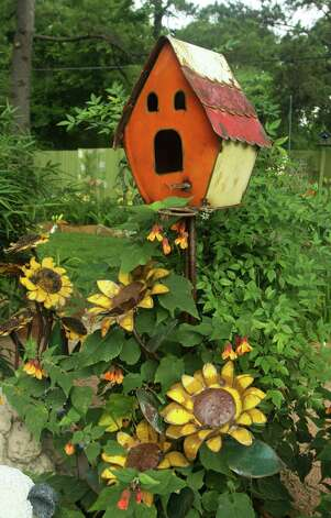 Loris Garrett believes diversity is the way to go in a display garden. A birdhouse with flowering maple and decorative sunflowers creates a focal point in the back garden. Photo: Gary Fountain, Freelance / Copyright 2012 Gary Fountain.