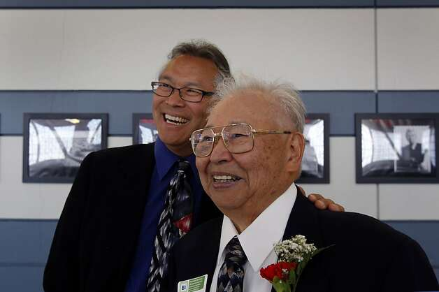 Paul Kitagaki, Jr. stands with his father during the opening of an exhibit of photographs by Dorothea Lange and Kitagaki, Jr. at the San Bruno BART station in San Bruno, Calif. on Saturday, April 28, 2012. After discovering a photograph of his own family, taken by Lange as they were being transferred to a World War II internment camp, Kitagaki launched a photography project to track down and photograph other subjects of Lange's work. Photo: Paul Chinn, The Chronicle