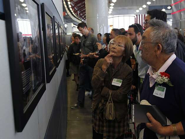 Judy Hamaguchi and Ivor Nii view an exhibit of photographs by Dorothea Lange and Paul Kitagaki, Jr. at the San Bruno BART station in San Bruno, Calif. on Saturday, April 28, 2012. After discovering a photograph of his own family, taken by Lange as they were being transferred to a World War II internment camp, Kitagaki launched a photography project to track down and photograph other subjects of Lange's work. Photo: Paul Chinn, The Chronicle