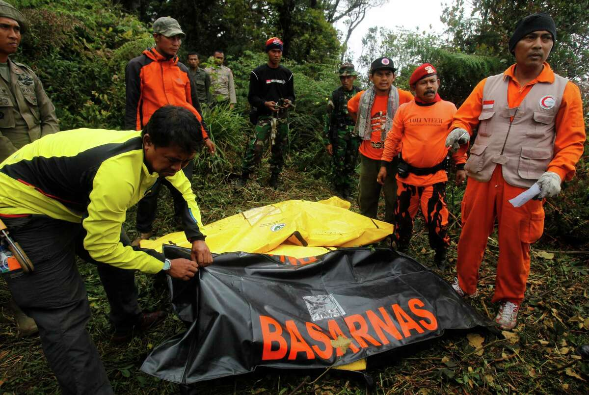 Indonesian rescue teams close plastic covers over the bodies of victims Friday after a Sukhoi Superjet-100 plane crashed at Mount Salak in Bogor, Indonesia Rescue teams used climbing gear to scale the nearly sheer slopes of a dormant Indonesian volcano, Friday, to reach the wreckage of the Russian-made jetliner that crashed Wednesday with 45 people aboard during a demonstration flight for potential buyers. The crash of a Russian-made passenger jet into the flanks of an Indonesian volcano has put a spotlight on the notoriously informal atmosphere aboard new aircraft during manufacturer demonstrations.