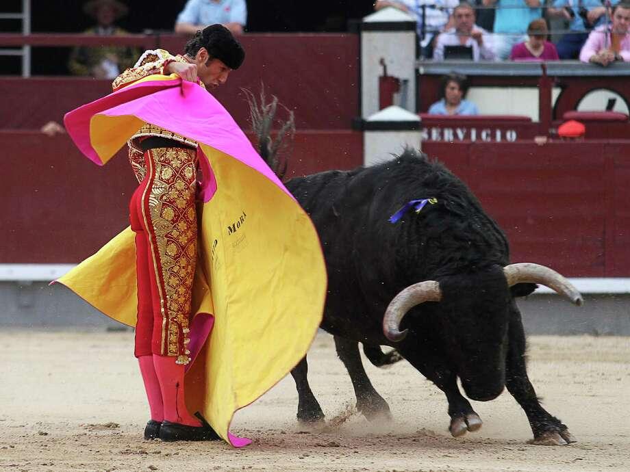 Spanish matador David Mora performs a pass to a bull during the San Isidro Feria at the Las Ventas bullring on May 11, 2012 in Madrid.   AFP PHOTO / ALBERTO SIMONALBERTO SIMON/AFP/GettyImages Photo: ALBERTO SIMON, AFP/Getty Images / AFP