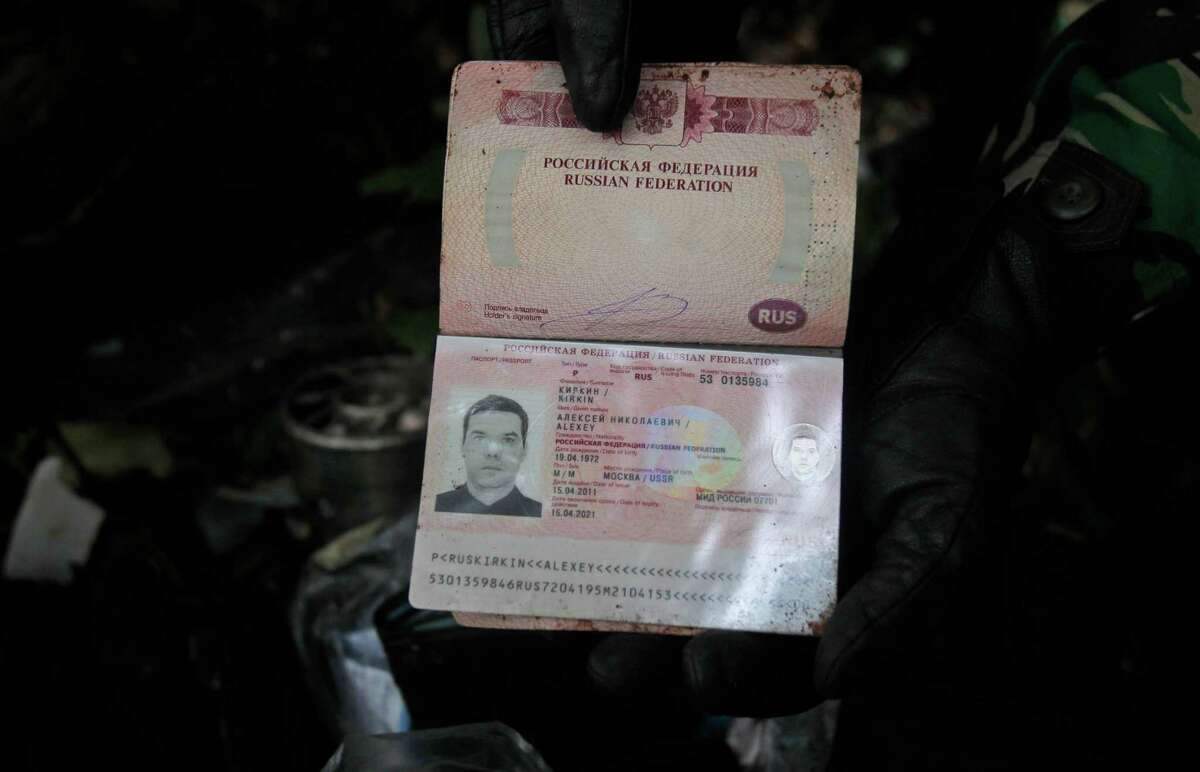 Passport of a pilot on the Sukhoi Superjet-100 is held by a rescue worker at Mount Salak in Bogor, Indonesia, Friday. Search teams who scaled a volcano's steep slopes found at least 12 bodies Friday near the wreckage of a Russian-made jetliner that crashed in Indonesia during a demonstration flight for potential buyers, an official said. All 45 aboard the Sukhoi Superjet-100 that crashed Wednesday are feared dead.