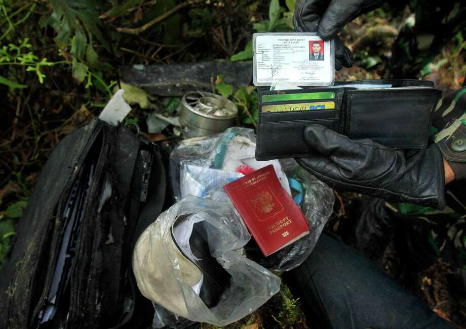 Documents and the passport of a passenger of the Sukhoi Superjet-100 is held by a rescue worker at Mount Salak in Bogor, Indonesia, Friday. Search teams who scaled a volcano's steep slopes found at least 12 bodies Friday near the wreckage of a Russian-made jetliner that crashed in Indonesia during a demonstration flight for potential buyers, an official said. All 45 aboard the Sukhoi Superjet-100 that crashed Wednesday are feared dead. Photo: Crack Palinggi, AP / AP