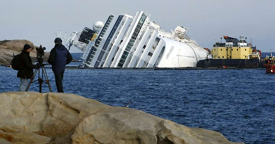 A barge is docked to the grounded cruise ship Costa Concordia off the Tuscan island of Giglio, Italy, Sunday, Feb. 5, 2012. The barge will serve as a staging platform for the removal of the 500,000 gallons (1.9 million liters) of heavy fuel oil that are aboard the ship. (AP Photo/Pier Paolo Cito) Photo: Pier Paolo Cito, Associated Press