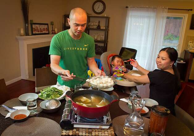 Chef James Syhabout of Commis puts fish balls in the Thai Hot Pot while Stacy Ly feeds their baby, Emma Syhabout at their home in Oakland, Calif., on Tuesday, May 1st, 2012. Photo: John Storey