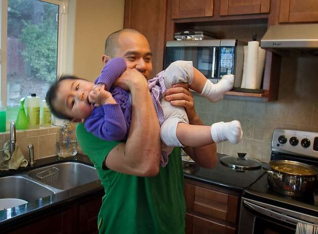 Chef James Syhabout holds how daughter Emma Syhabout at his home for his family in Oakland, Calif., on Tuesday, May 1st, 2012. Photo: John Storey