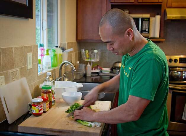 Chef James Syhabout of Commis cuts green onions for a garnish for the Thai Hot Pot is was making for his family in Oakland, Calif., on Tuesday, May 1st, 2012. Photo: John Storey